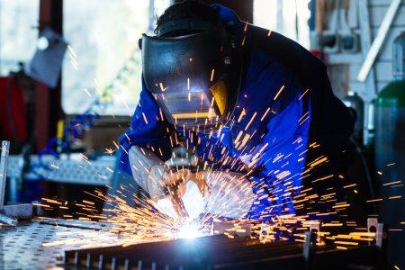 Photo pour Soudeur soudant du métal avec dispositif de soudage en atelier, beaucoup d'étincelles à voir, il porte des googles de soudage - image libre de droit