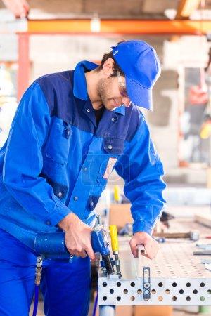 Photo pour Métal rivet artisan avec de l'air comprimé pistolet en atelier - image libre de droit