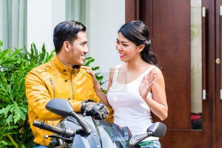 Photo pour Femme, dire au revoir à motocycliste qui est monté au large de travailler le matin - image libre de droit