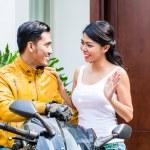 Постер, плакат: Woman saying goodbye to motorcyclist