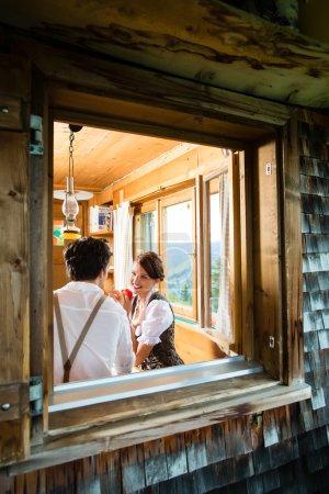 Photo pour Couple dans une cabane de montagne traditionnelle prenant un repas - vue par la fenêtre - image libre de droit