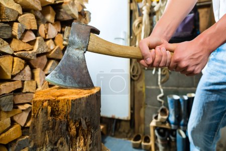 Young man chopping fire wood in mountain chalet