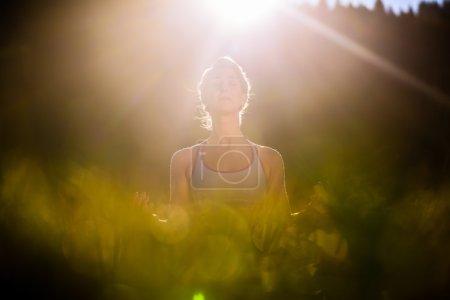 Photo pour Femme faisant du yoga au coucher du soleil, situation rétro-éclairée - image libre de droit
