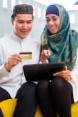 Asijské muslimský pár online nakupování na podložce v obývacím pokoji