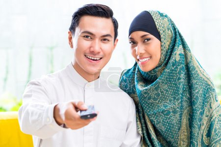 Asian Muslim Couple switching TV with remote control