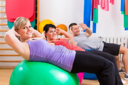 Patients at physiotherapy on training balls
