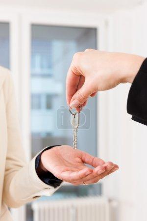 Photo pour Jeune agent immobilier donne les clés d'un appartement au locataire, gros plan sur les clés et les mains - image libre de droit