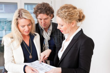 realtor explaining ground plan to couple