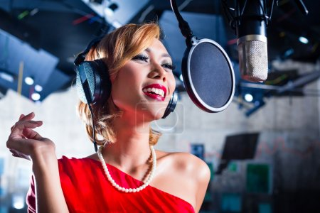 Photo for Asian professional musician recording new song or album CD in studio - Royalty Free Image