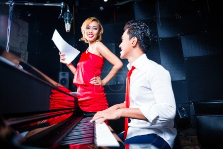 Asian professional musician recording song in studio