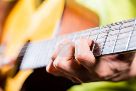 Asian guitarist playing music in recording studio