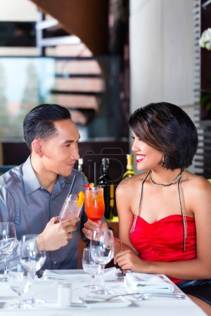 Asian couple drinking cocktails in bar