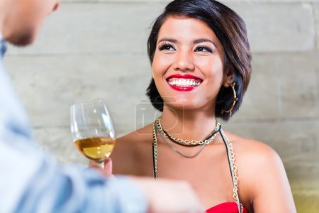 Asian couple clinking wine glasses in bar