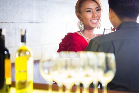 Asian couple drinking white wine in bar