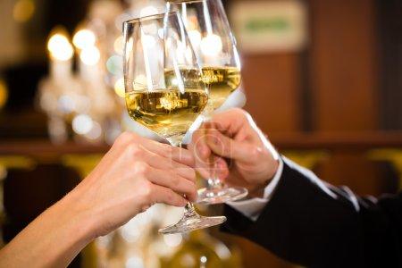 Photo pour Heureux couple a un rendez-vous romantique dans une amende restaurant gastronomique qu'ils boivent le vin et tinter les verres, acclamations - closeup - image libre de droit