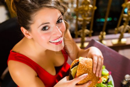 woman in fine restaurant, she eats a burger