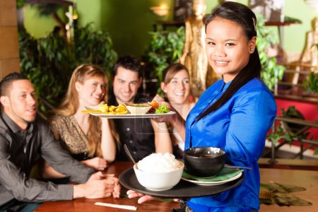 Photo for Young people eating in a Thai restaurant; the waitress brings the dishes, rice and others - Royalty Free Image