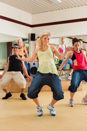 Photo pour Zumba ou Jazzdance - jeunes dansant dans un studio ou un gymnase faisant du sport ou pratiquant un numéro de danse - image libre de droit