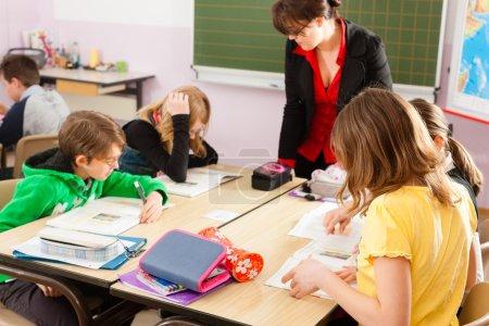 Foto de Educación - alumnos y profesor de aprendizaje en la escuela elemental o primaria en el aula - Imagen libre de derechos