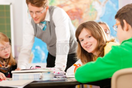 Photo for Education - Pupils and teacher learning at elementary or primary school in the classroom - Royalty Free Image