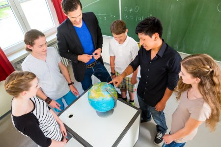 Photo pour École Étudiants ou élèves ou compagnons ayant un travail de groupe pendant la leçon de géographie et l'enseignant les testent ou les éduquent à l'école ou en classe - image libre de droit
