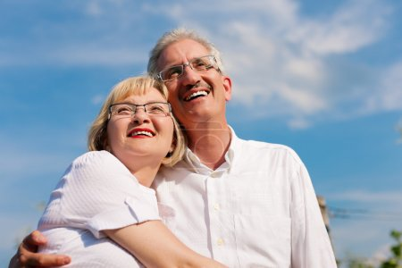 Happy senior couple looking to the blue sky