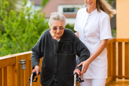 nurse and female senior with walking frame