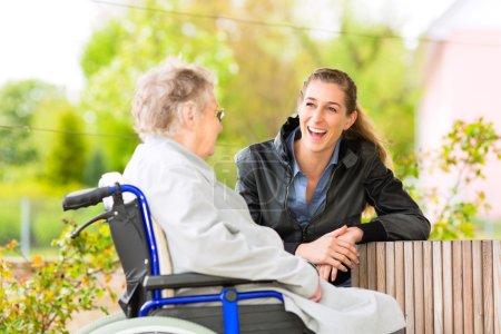 Photo pour Jeune femme rend visite à sa grand-mère en maison de retraite - image libre de droit