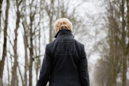 Photo for Depressed or sad woman walking down a barren path in winter - Royalty Free Image
