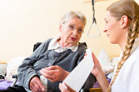 Photo for Nurse taking care of senior woman in retirement home bandaging a wound - Royalty Free Image