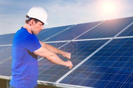 Foto de Sistema fotovoltaico con paneles solares para la producción de energía renovable a través de energía solar, un técnico que utiliza un destornillador o una herramienta - Imagen libre de derechos