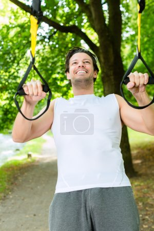 man in city park doing suspension trainer sport