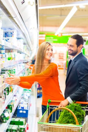 Couple selecting cooled products in hypermarket