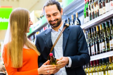 Couple selecting wine in supermarket