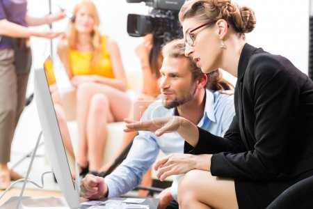 Photo for Team or Director discussing during a break the scene direction on set of a commercial video production or reportage at a screen - Royalty Free Image