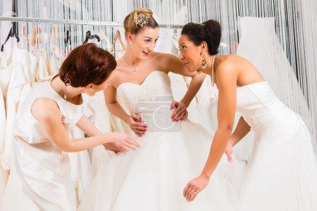 Women having fun during bridal dress fitting in shop