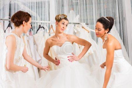 Photo pour Les femmes s'amusent pendant la robe de mariée montage dans le magasin de mode de mariage - image libre de droit