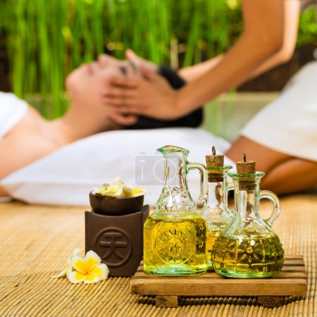 Photo for Beautiful Asian woman having a wellness Head massage in a tropical setting and feeling visibly good about it - Essential oils are in the foreground - Royalty Free Image
