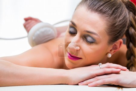 Woman having back massage in wellness spa