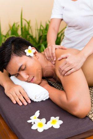 Photo pour Indonésien asiatique homme dans bien-être beauté spa ayant aromathérapie massage à l'huile essentielle, l'air détendu - image libre de droit