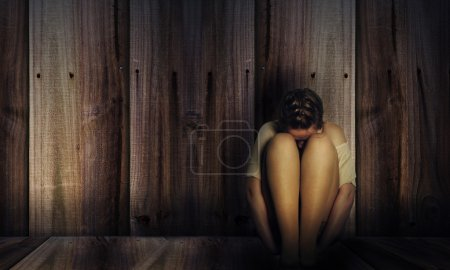 Photo for Depressed girl sitting near the wall - Royalty Free Image