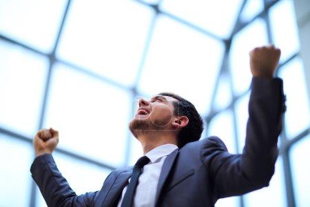 Photo pour Homme d'affaires prospère avec les bras levés célébrant sa victoire - image libre de droit