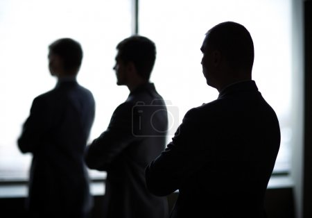 Silhouette of three businessmen in the office