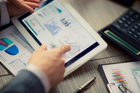 Photo pour Homme d'affaires en ligne Évaluation financière sur tablette. Travail d'équipe au bureau - image libre de droit