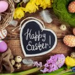 Black board with text - Happy Easter. Colorful Easter Eggs and flowers