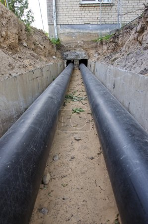 New plastic modern heating pipes in trench near city house