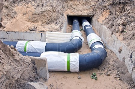 plastic modern  black heating pipes in trench near city house