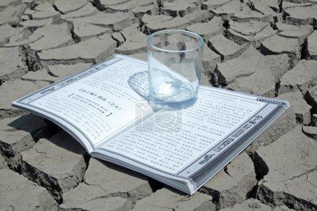 Photo pour Gros plan du livre et de la coupe en terre sèche, des images créatives, métaphore de la connaissance comme l'eau de source, comme c'est indispensable à la population. - image libre de droit