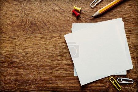 Photo pour Fournitures de bureau assorties telles que papiers propres, crayon, punaises et clips sur la table en bois, reposant au bord inférieur avec espace de copie ci-dessus pour les textes . - image libre de droit