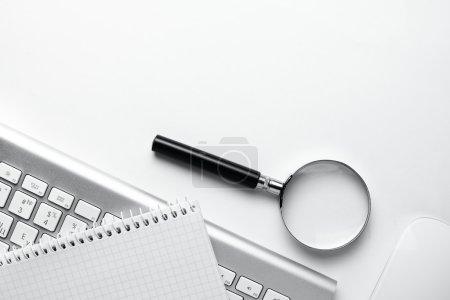 Photo pour Image conceptuelle décrivant la réalisation d'une recherche en ligne pour plus d'informations avec une loupe sur un cahier vierge aux côtés d'un clavier et une souris d'ordinateur sans fil - image libre de droit